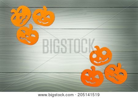 Top view of paper silhouette of six different pumpkin made of vertical frame on grey wooden background. Halloween holiday background. Copy space