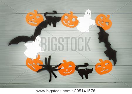 Halloween holiday background made of frame with pumpkins, bats, cats, spiders and ghosts cut paper on gray board. Copy space. Light up