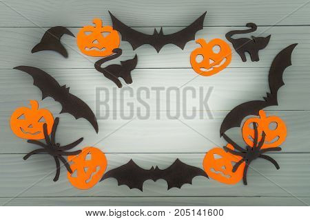 Halloween holiday background made of frame with pumpkins, bats, cats, spiders and hat cut paper on gray board. Copy space. Light up