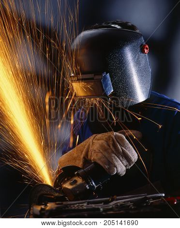 Metalworker with an electric drill cutting a piece of metal and producing lot of sparks.