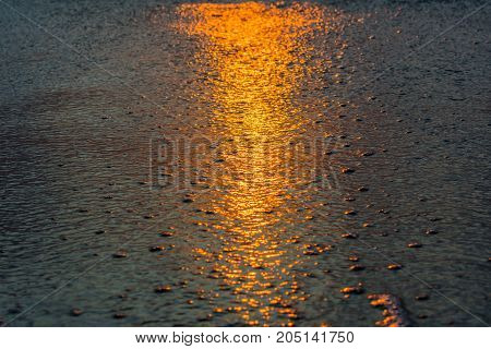 textured background - close up of ocean water on the sand reflecting the orange light of sunrise