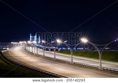 Illuminated empty highway at night. Long exposure cityscape