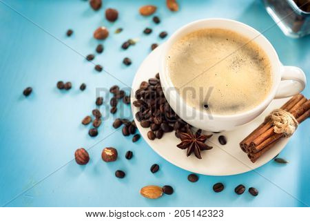 Cup of fresh coffee on blue wooden background,
