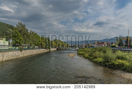 Vah river in Ruzomberok town with cloudy blue sky in summer day