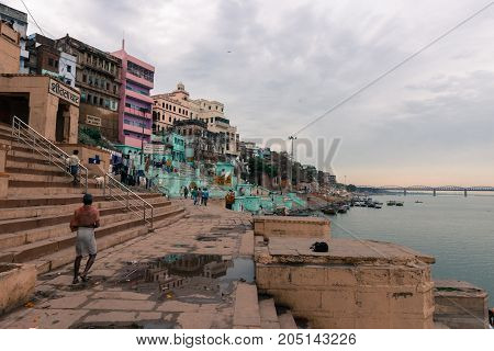 VARANASI INDIA - MARCH 13 2016: Wide angle picture of the stairs and houses at Lal Ghat in front of Ganges River in the city of Varanasi in India
