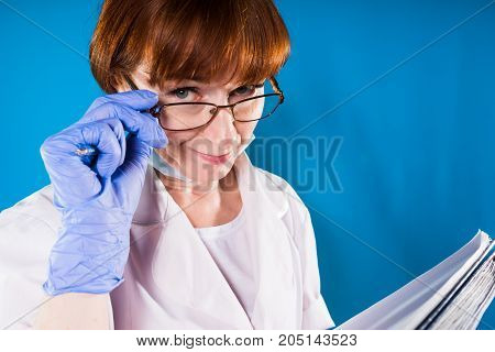 Funny female doctor looks skeptically at camera and takes off glasses, suspects not trusting