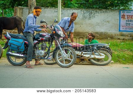 AGRA, INDIA - SEPTEMBER 19, M 2017: Unidentified man rides a motorcycle, while other man is helping his friend that felldown from his motorcycle, in the streets in central India in Agra, India.