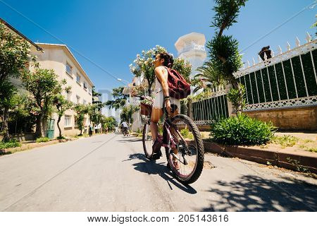 Happy woman on bicycle,summer background with tropical trees and flowers
