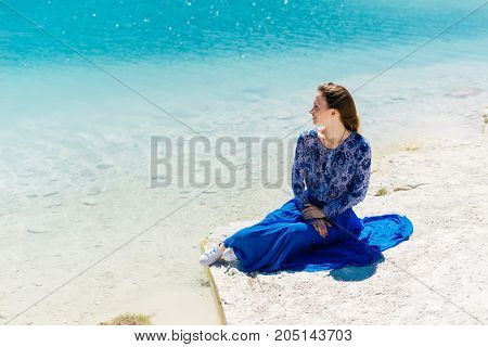 Freedom woman in free happiness bliss on beach. Smiling happy multicultural female model in summer dress enjoying serene ocean nature during travel holidays vacation outdoors,sitting.Dental.