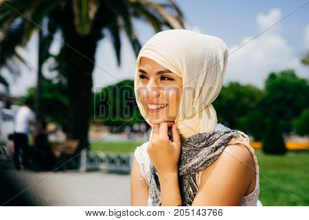 A happy emotional Muslim girl in a scarf is sitting in the park