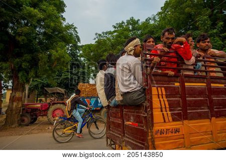 AGRA, INDIA - SEPTEMBER 19, 2017: Crowd of people in the back part of a car in the streets in central city in Agra, India.
