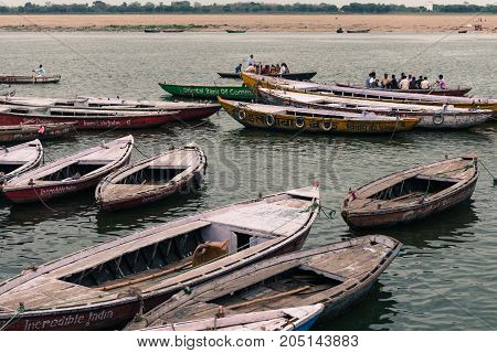 VARANASI INDIA - MARCH 13 2016: Horizontal picture of many docked boats during daytime at Ganges River in the city of Varanasi in India