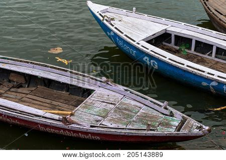 VARANASI INDIA - MARCH 13 2016: Close picture of two docked boats during daytime at Ganges River in the city of Varanasi in India