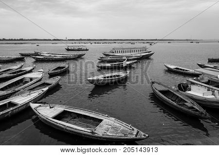 VARANASI INDIA - MARCH 13 2016: Black and white picture of many docked boats during daytime at Ganges River in the city of Varanasi in India