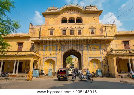 JAIPUR, INDIA - SEPTEMBER 19, 2017: Unidentified people riding motorcycles and bikes and driving cars through the City Palace, a palace complex in Jaipur, Rajasthan, India.