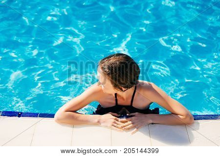 Beautiful Sexy Woman Relaxing In Swimming Pool Water. Girl With Healthy Tanned Skin, Gorgeous Face, And Wet Hair Enjoying Summer Sun On Hot Summer Day At Pool Edge At Luxury Resort