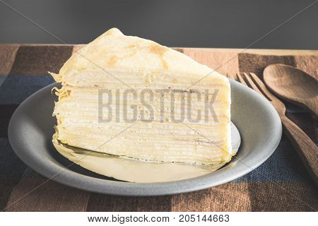 Crepe Cake Or Milk Cake In A Plate With Wooden Spoon And Fork On Table Cloth