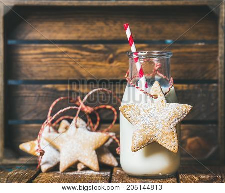 Christmas festive gingerbread star shaped cookies and bottle with milk and straw, wooden background. Selective focus, copy space, horizontal composition