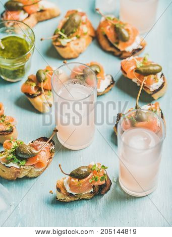 Crostini with smoked salmon, pesto sauce, watercress and capers and pink grapefruit cocktails in glasses over light blue background, selective focus. Party, catering or fingerfood concept
