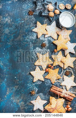 Gingerbread Christmas star shaped cookies with cinnamon, anise, nuts, baking molds and sugar powder on dark plywood painted background, top view, copy space, verticall composition