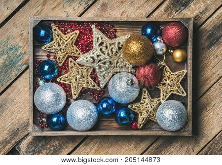 Christmas or New Year holiday decoration background. Christmas tree glittering toy stars, balls and garland in wooden box over rustic wooden background, top view, horizontal composition