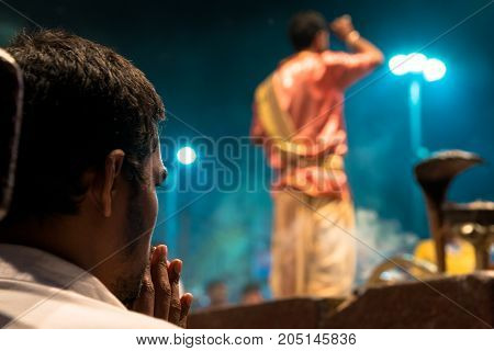 VARANASI INDIA - MARCH 13 2016: Horizontal picture of unidentified Hindu indian man praying during Ganga Aarti ritual at Dashashwamedh Ghat in Varanasi India.