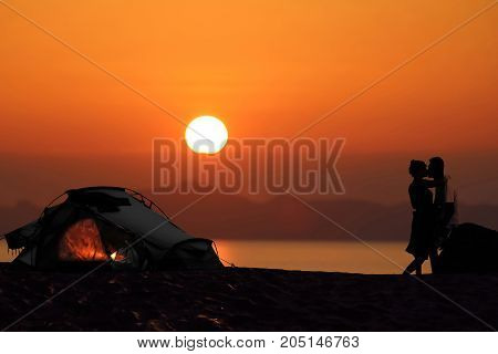 Silhouette romantic couple camping with tents on the beach during sunset background