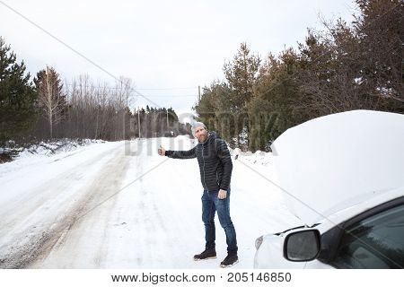 A young handsome man in black jacket in winter, stood on the highway and hitchhiking.