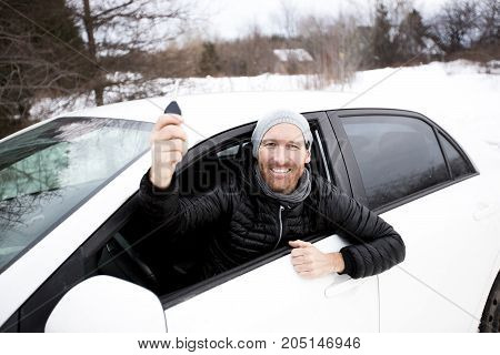 A Portrait of handsome man in car in winter
