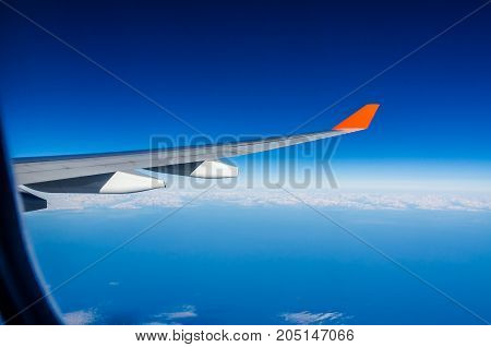 Plane wing white clouds and blue sky