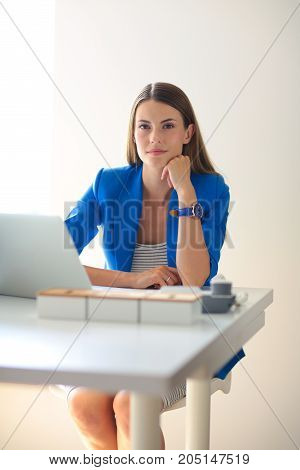 Woman with documents sitting on the desk.