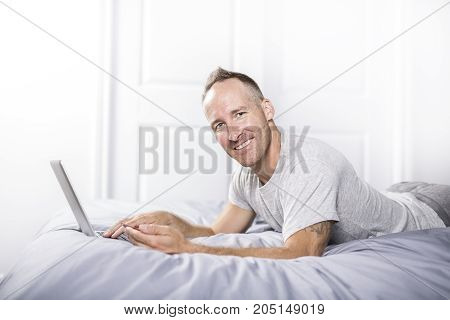 A Serious casual young man using laptop in bed at home