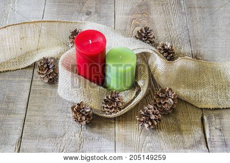 Red and green candles wrapped simply with burlap cloth and surrounded by pinecones on rustic wooden table. Christmas or autumn image