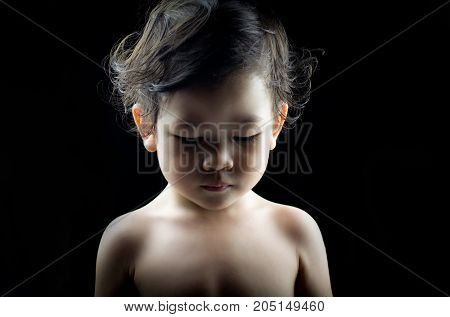 Portrait of baby child face is nervousness or anxiety and feels insecure isolated on black background. Domestic violence concept child abuse concept