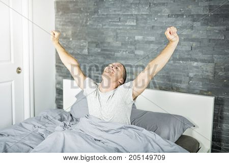 A Cheerful young man waking up in bed and stretching his arms