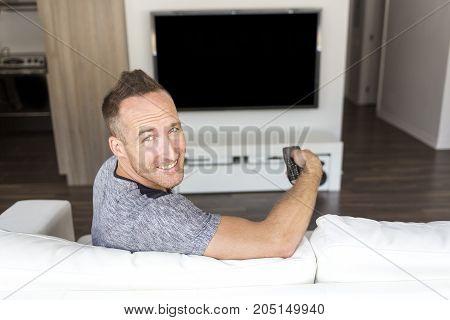 A nice man on sofa linstening TV