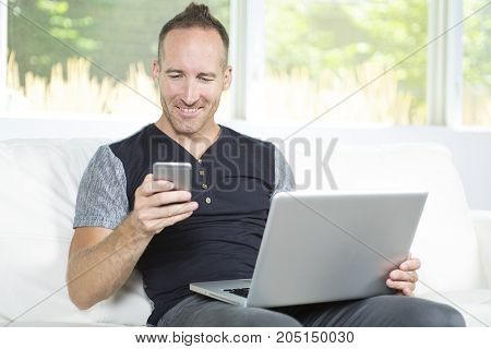 A Front view of a handsome man using a laptop sitting on couch at home