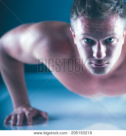 Fitness man doing push ups on floor .