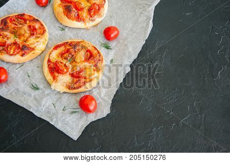 Mini Pizzas Margheritas Served On A Baking Paper. Black Stone Background.