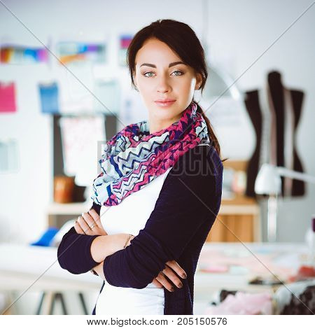 Beautiful young fashion designer standing in studio .