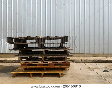 pile of old wood pallet on dirty ground in front of steel wall in industry