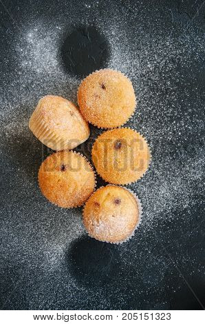 Set Of Vanilla Muffins With Chocolate Cream Filling Sprinkled With Powdered Sugar. Black Stone Backg