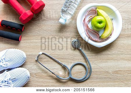 Healthy lifestyle for women diet with sport equipment sneakers measuring tape fruit healthy green apples and bottle of water on wooden. Healthy Concept.