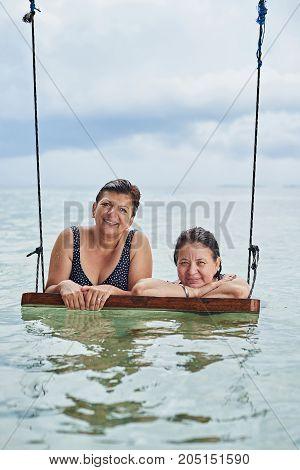 Two old woman hang on swings in caribbean sea