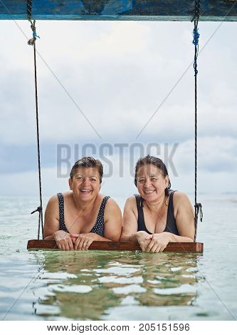 Two happy smling old woman on sea water. Mature womans on vacation
