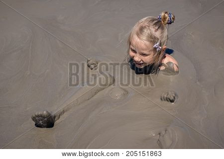 A little girl receives medical treatments in a mud volcano. Treatment of diseases using alternative medicine.
