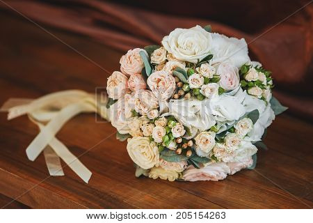 Beautiful wedding bouquet of roses on wooden background closeup. Marriage concept