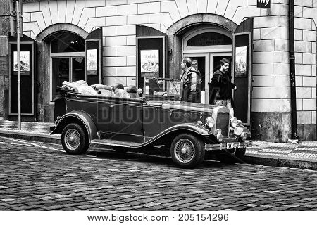 PRAGUE CZECH REPUBLIC - FEBRUARY 02 2014: Tour of the city on an old car. Black and white. Stylized film. Prague is the capital and largest city of the Czech Republic.