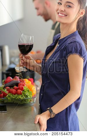 Couple drinking wine while cooking in the kitchen.