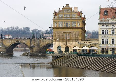 PRAGUE CZECH REPUBLIC - FEBRUARY 02 2014: The Smetana Museum (Muzeum Bedricha Smetany) and the famous Charles Bridge on the Vltava River. Prague is the capital and largest city of the Czech Republic